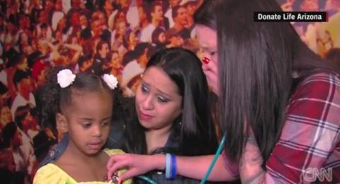 Una madre escucha el corazón de su hijo latir en otra pequeña