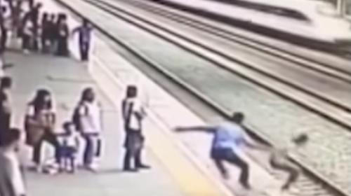 Un hombre salva a una mujer antes de caer en las vías del tren