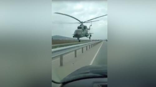 Un helicóptero asombra al volar cerca de una carretera
