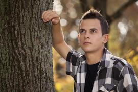 Muchacho recostado en un árbol con gesto dubitativo