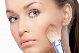 Mujer se aplica polvos en el rostro con una brocha